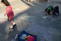 Nens pintant el terra amb guixos