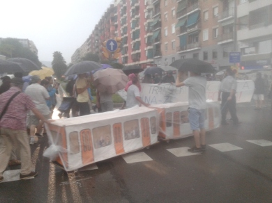 Els veïns han desafiat el xàfec durant el tall de carrer que ha impedit el trànsit al Passeig de la Zona Franca / Mar Romero